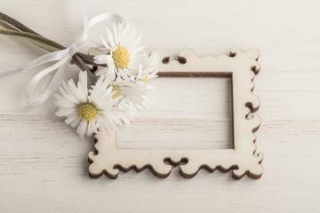daisy flowers and an empty frame on wooden background