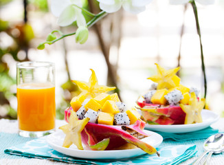 Tropical fruit salad in pitahaya, mango, dragon fruit bowls with a glass of juice Diet, healthy fruit salad Healthy breakfast, weight loss concept