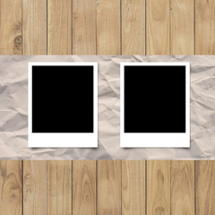 Blank photo frame on White paper on wood planks texture backgrou