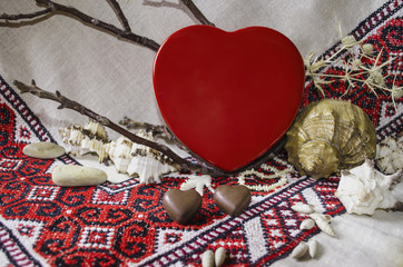Chocolates and red box as a heart against the background embroidered tablecloths