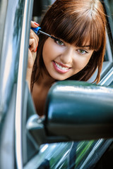 Portrait of young woman making herself up in car