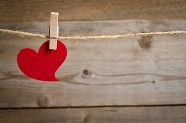 Red fabric heart  hanging on the clothesline. On old wood backgr