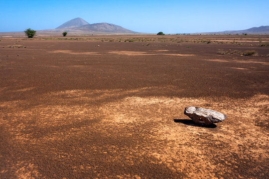 Single rock, empty flat desert field Sal, Cape Verde