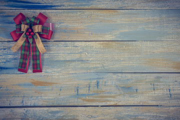 Christmas fabric bow on colored wooden background