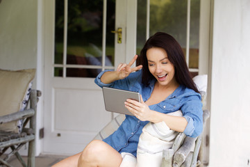 Young woman making peace hand sign with chat video