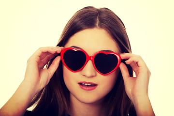 Shocked teen woman wearing sunglasses.