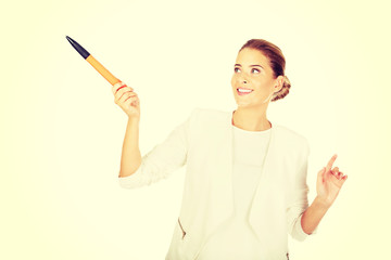 Young businesswoman points something big pen
