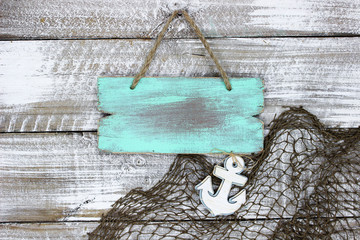 Blank wood mint green sign and fish net with anchor hanging wood background
