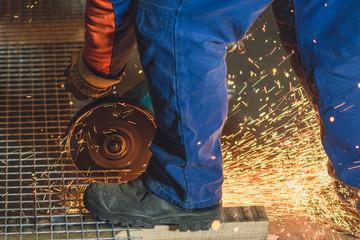 Worker grinding a metal