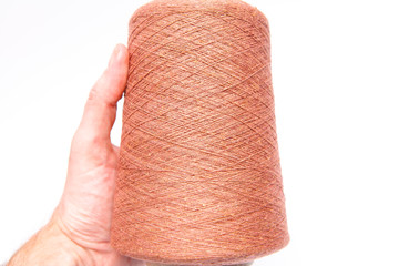 The hand holds a skein of colored wool threads