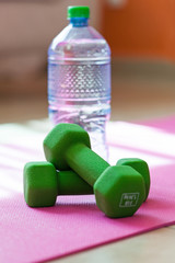 Two dumbbells with mineral water on yoga mat