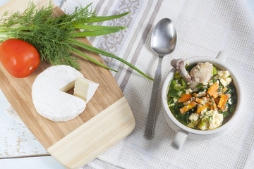 Cheese soup with chicken, herbs and vegetable. Camembert, tomato and herbs on wooden board. Light background