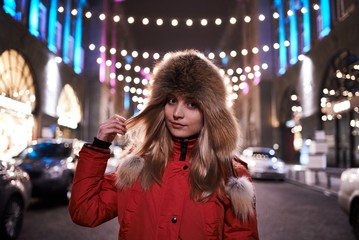 Portrait of the girl on the night and light street of Kyiv in winter.