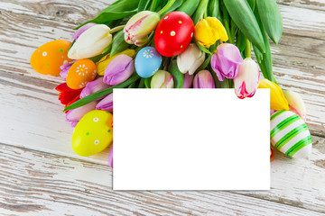 Colorful tulips with eggs on wooden table.