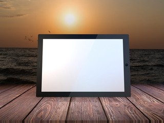 Tablet computer on sea background