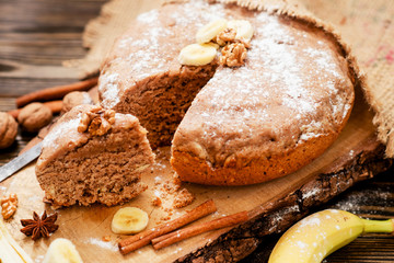 pastries, cake with walnuts and a banana with powdered sugar on a wooden background