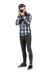 Hipster in plaid shirt taking photo with dslr camera looking at camera. Full body length portrait isolated over white studio background.