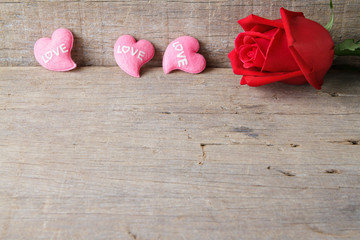Valentines day background with pink hearts and rose on wooden ba
