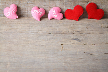 Valentines day background with red and pink hearts on wooden bac