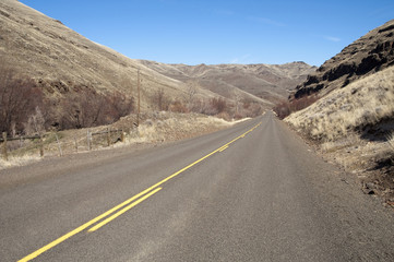 Lonely Tow Lane Divided Highway Cuts Through Dry Hills Landscape