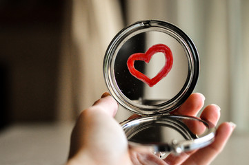 Holding a mirror with a heart drawn by a lipstick. valentine's day