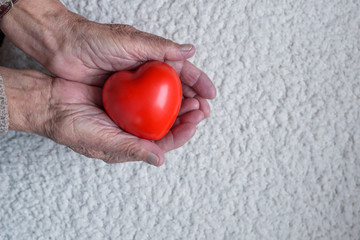 Red heart in old woman hands