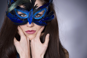 Woman Wears Feather Mask over her Eyes