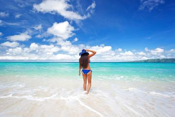 Enjoying freedom. Beautiful woman on beach in summer hat