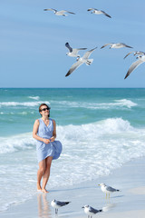 Young woman feeding seagulls on tropical beach, Florida