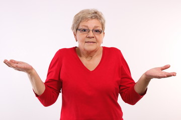 Elderly woman shrugging shoulders and throwing up her hands, emotions in old age