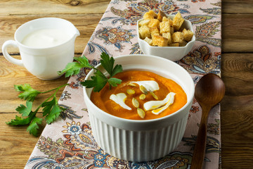 Autumnal spicy pumpkin squash cream soup with cream, parsley and pumpkin seeds and in the white bowl, cream in a creamer and croutons in a serving dish on the napkin on rustic wooden background