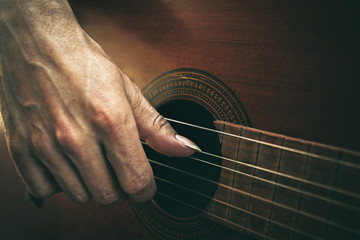 guitarist hand on strings macro. playing acoustic guitar.