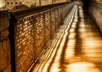 Silhouette of a man walking at night on the bridge.