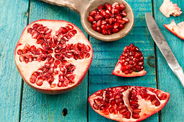 Ripe pomegranate fruit on wooden vintage background. Healthy vegetarian food. Recipe, menu, mock up, cooking.