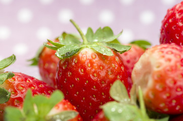Fresh red ripe strawberries on a plate. Pink dotted background.