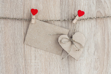 blank paper card with heart hanging on wooden background