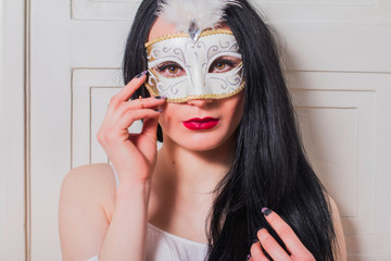 Portrait of beautiful mysterious young woman in carnival mask on the door, beauty fashion concept