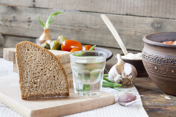 Still life with horilka (vodka) and sliced bread on wooden board