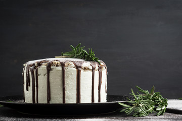 Creamy cake with chocolate glaze on the rustic background