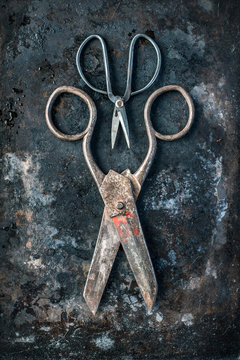 Two pairs of antique scissors on weathered rusty background