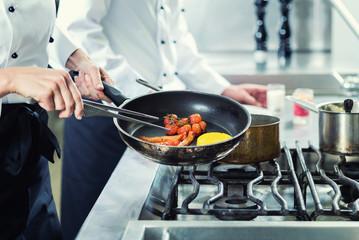 Zwei Köche in Hotelküche braten Gemüse in Pfanne