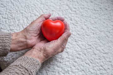 Old woman hands holding red heart, closeup shot