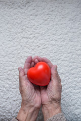 Old woman hands with red heart