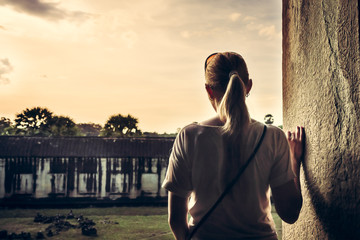 young woman standing at the edge of building and looking at view during sunset through ancient window with copy space