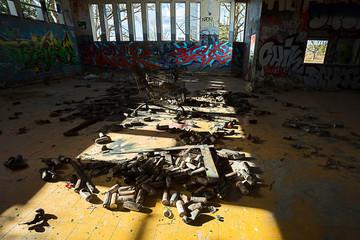 Un tas de bombe de peinture sur le sol d'un bâtiment couvert de graffiti