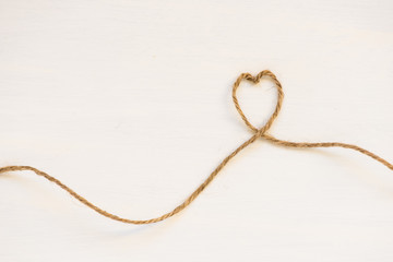 Heart made from string on white background