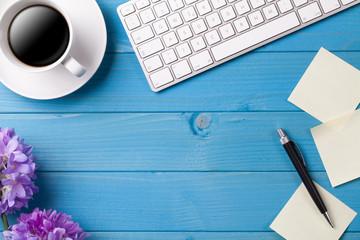 Schreibtisch mit Kaffee, Tastatur und Blumen