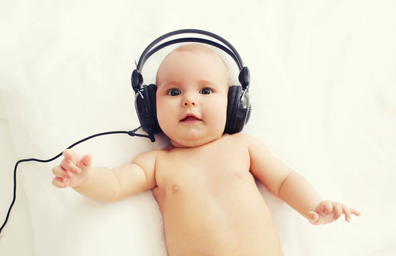 Beautiful baby listens to music in headphones lying on bed, top