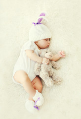 Sweet baby sleeping with teddy bear toy on white soft bed at hom
