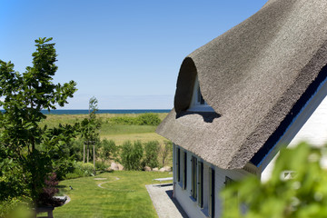 historical house with thatched roof and blue sky at the German Baltic Sea coast, Germany, Europe